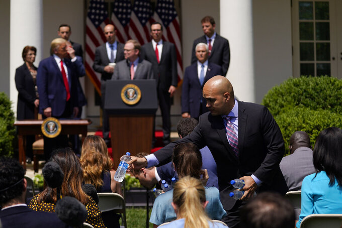 Water is handed out to members of the press as President Donald Trump holds a news conference in the Rose Garden of the White House, Friday, June 5, 2020, in Washington. (AP Photo/Evan Vucci)