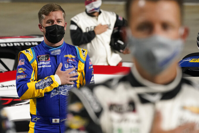 Justin Allgaier, left, and AJ Allmendinger, front, stand during the national anthem before the NASCAR Xfinity Series auto race at Martinsville Speedway in Martinsville, Va., Friday, April 9, 2021. (AP Photo/Steve Helber)