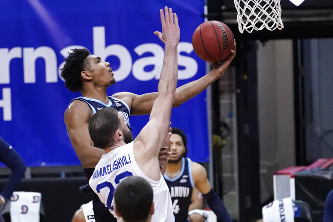 Villanova forward Jermaine Samuels, top, goes to the basket past Seton Hall forward Sandro Mamukelashvili (23) during the second half of an NCAA college basketball game, Saturday, Jan. 30, 2021, in Newark, N.J. (AP Photo/Mary Altaffer)