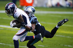 Denver Broncos wide receiver KJ Hamler scores past Carolina Panthers cornerback Rasul Douglas during the second half of an NFL football game Sunday, Dec. 13, 2020, in Charlotte, N.C. (AP Photo/Brian Blanco)