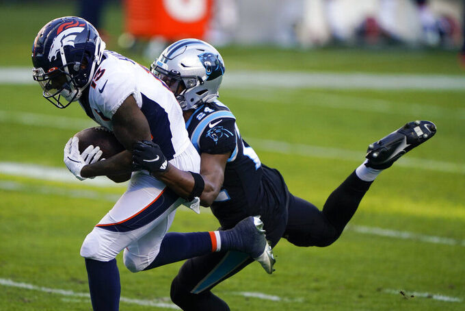 Denver Broncos wide receiver KJ Hamler scores past Carolina Panthers cornerback Rasul Douglas during the second half of an NFL football game Sunday, Dec. 13, 2020, in Charlotte, N.C. (AP Photo/Brian Blanco)