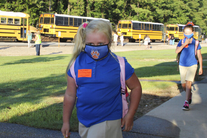 Following direction, McCartney Moulds, 6, a second-grader, distances herself from a fellow student as she walks to class with full mask following her bus commute, to the Newton County Elementary School in Decatur, Miss., Monday, Aug. 3, 2020. Thousands of students across the nation are set to resume in-person school Monday for the first time since March. Parents are having to balance the children's need for socialization and instruction that school provides, with the reality that the U.S. death toll from the coronavirus has hit about 155,000 and cases are rising in numerous places. (Janine Vincent/Newton County Schools via AP)