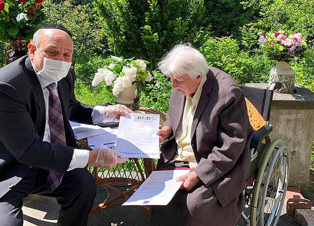Poland's chief rabbi, Michael Schudrich, delivers letters with birthday greetings from the Israeli and Polish presidents, to Anna Kozminska, a 101-year-old Polish woman who is believed to the be oldest living person recognized by Yad Vashem for rescuing Jews during the Holocaust, in Warsaw, Poland, on Friday, May 22, 2020. Both Reuven Rivlin of Israel and Andrzej Duda of Poland praised Kozminska in letters for her courage in risking her own life help Jews during the German occupation of Poland. (Grazyna Pawlak via AP)