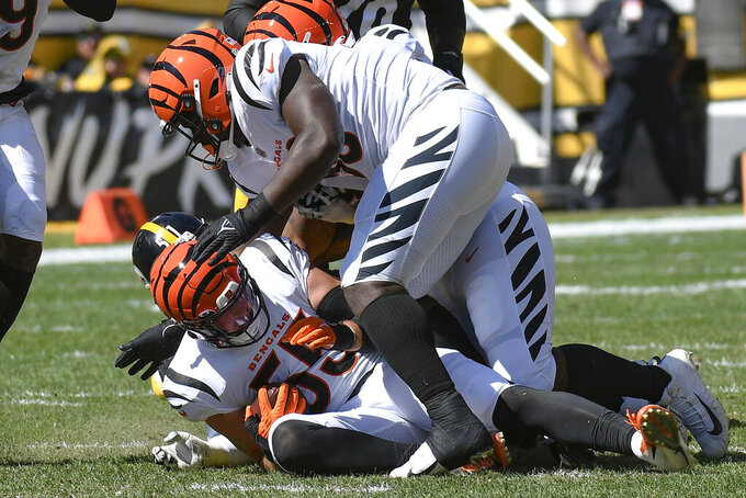 Cincinnati Bengals linebacker Logan Wilson (55) celebrates with teammates after making an interception of a pass by Pittsburgh Steelers quarterback Ben Roethlisberger during the first half an NFL football game, Sunday, Sept. 26, 2021, in Pittsburgh. (AP Photo/Don Wright)
