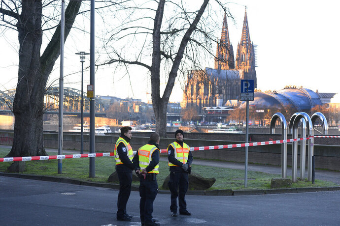 Employees of the public order office block a road close to the Cologne Cathedral in Cologne, Germany, Tuesday, Jan. 21, 2020. A train station, an opera house and a TV station in the western Germany city of Cologne are evacuated on Tuesday as experts prepare to defuse an American 500-kilogram (1,100-pound) bomb from World War II. (Roberto Pfeil/dpa via AP)