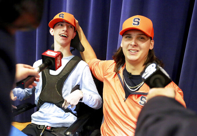 Hanahan High School football player Cooper Dawson, right, talks to the media after first letting his friend and fellow senior Kingsley Feiman announce that he would play football at Syracuse University on early signing day in Hanahan, S.C., Wednesday, Dec. 19, 2018. (Brad Nettles//The Post And Courier via AP)