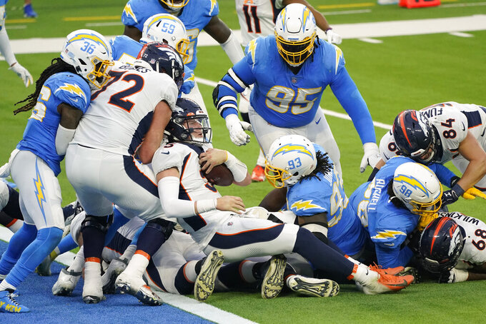 Denver Broncos quarterback Drew Lock, bottom center, pushes into the end zone for a touchdown during the second half of an NFL football game against the Los Angeles Chargers Sunday, Dec. 27, 2020, in Inglewood, Calif. (AP Photo/Ashley Landis)