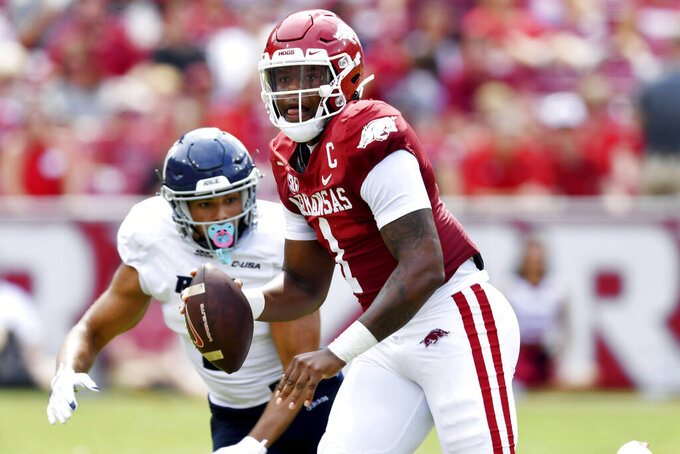Arkansas quarterback KJ Jefferson (1) tries to get away from Rice defender JoVoni Johnson (3) as he scrambles out of the pocket during the first half of an NCAA college football game Saturday, Sept. 4, 2021, in Fayetteville, Ark. (AP Photo/Michael Woods)