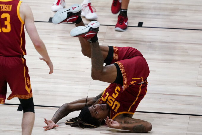 Southern California guard Isaiah White (5) falls to the court during the second half of an Elite 8 game against Gonzaga in the NCAA men's college basketball tournament at Lucas Oil Stadium, Tuesday, March 30, 2021, in Indianapolis. (AP Photo/Michael Conroy)