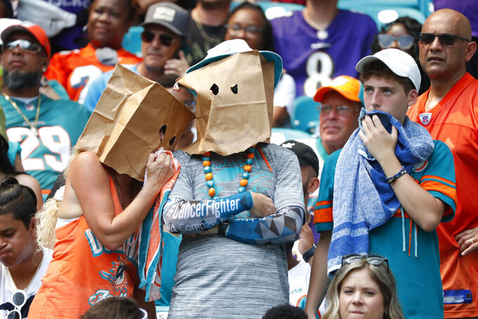 FILE - In this Sept. 8, 2019, file photo, Miami Dolphins fans shows his displeasure with the team during the first half at an NFL football game against the Baltimore Ravens, in Miami Gardens, Fla. The Dolphins look like the worst team in the NFL, and might even be the worst team in Miami. On the other hand, a comparison with the Marlins is one matchup the Dolphins might win. (AP Photo/Wilfredo Lee, File)
