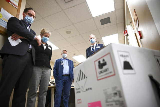 From left, North Memorial Systems Director of Pharmacy Services Paul Krogh, Chief Administrative Officer Samantha Hanson, Vice President of Operations Steve Horstmann and CEO Dr. Kevin Croston took a moment, in silence, and looked at the box containing 975 doses of the COVID-19 vaccine which just arrived at North Memorial Health Hospital, Tuesday, Dec. 15, 2020 in Robbinsdale, Minn. (Aaron Lavinsky/Star Tribune via AP, Pool)