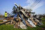 In the aftermath of Hurricane Ida, a man scavenges for copper in a debris pile, Sunday, Sept. 5, 2021, in Montz, La. (AP Photo/Matt Slocum)