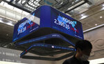 A man wearing a face mask walks near a screen showing the Korea Composite Stock Price Index (KOSPI) at the Korea Exchange in Seoul, South Korea, Thursday, Oct. 8, 2020. Asian shares were mostly higher Thursday on optimism that U.S. stimulus may be coming, as President Donald Trump appeared to reverse his earlier decision to halt talks on another economic rescue effort. (AP Photo/Lee Jin-man)