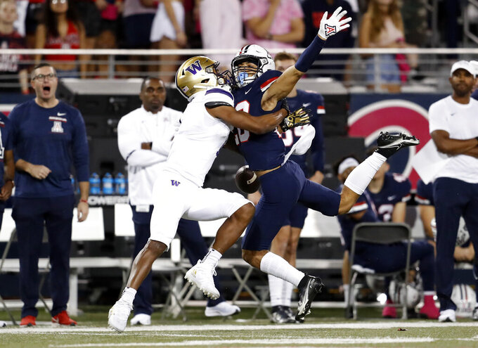 Arizona cornerback Treydan Stukes (20) breaks up a pass intended for Washington wide receiver Terrell Bynum (1) during the first half of an NCAA college football game Friday, Oct. 22, 2021, in Tucson, Ariz. (AP Photo/Chris Coduto)