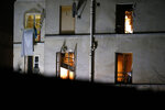 FILE - In this Nov. 18, 2015 file photo bullet holes and smashed windows are pictured on the back side of the house after an intervention of security forces against a group of extremists in Saint-Denis, near Paris. (AP Photo/Michel Euler, File)