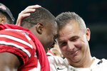 FILE - In this Dec. 2, 2018, file photo, Ohio State head coach Urban Meyer and wide receiver Terry McLaurin, left, celebrate early after defeating Northwestern 45-24 in the Big Ten championship NCAA college football game in Indianapolis. Meyer, the highly successful coach who won three national championships and sparked controversy and criticism this season for his handling of domestic violence allegations against a now-fired assistant, will retire after the Rose Bowl, the university announced Tuesday, Dec. 4, 2018.(AP Photo/Michael Conroy, File)