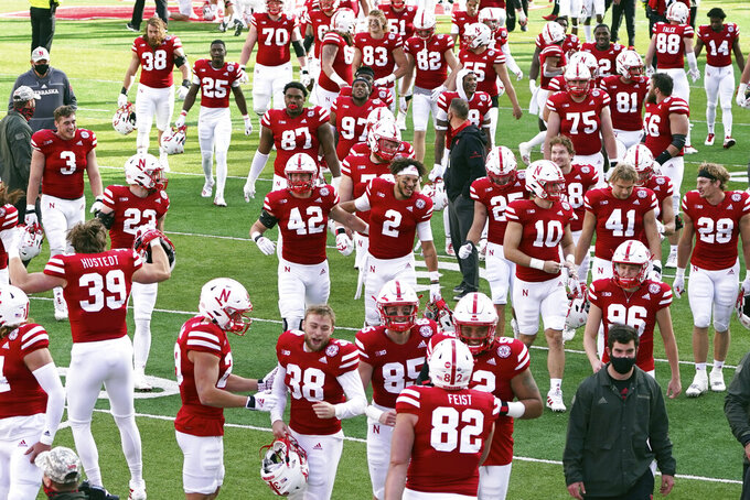 Happy Nebraska players run off the field following their first win of the season against Penn State, in an NCAA college football game in Lincoln, Neb., Saturday, Nov. 14, 2020. Nebraska won 30-23. (AP Photo/Nati Harnik)