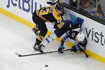 Boston Bruins center Charlie Coyle (13) and Winnipeg Jets defenseman Neal Pionk (4) compete for the puck along the boards during the first period of an NHL hockey game Thursday, Jan. 9, 2020, in Boston. (AP Photo/Elise Amendola)