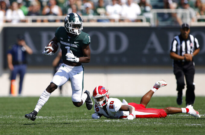 Michigan State receiver Jayden Reed, left, runs against Youngstown State's Natavious Payne (20) during the first quarter of an NCAA college football game, Saturday, Sept. 11, 2021, in East Lansing, Mich. Michigan State won 42-14. (AP Photo/Al Goldis)