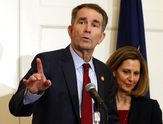 FILE - In this Feb. 2, 2019 file photo Virginia Gov. Ralph Northam, left, gestures as his wife, Pam, listens during a press conference in the Governors Mansion at the Capitol in Richmond, Va. Northam is actively campaigning for Democratic legislative candidates ahead of Election Day (AP Photo/Steve Helber, File)