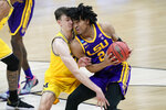 Michigan guard Franz Wagner, left, tries to steal the ball from LSU forward Trendon Watford (2) during the first half of a second-round game in the NCAA men's college basketball tournament at Lucas Oil Stadium Monday, March 22, 2021, in Indianapolis. (AP Photo/AJ Mast)