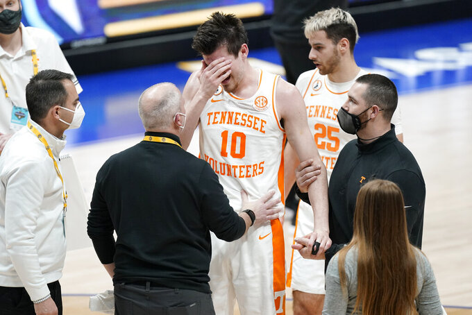 Tennessee's John Fulkerson (10) is helped up after being fouled by Florida's Omar Payne in the second half of an NCAA college basketball game in the Southeastern Conference Tournament Friday, March 12, 2021, in Nashville, Tenn. (AP Photo/Mark Humphrey)