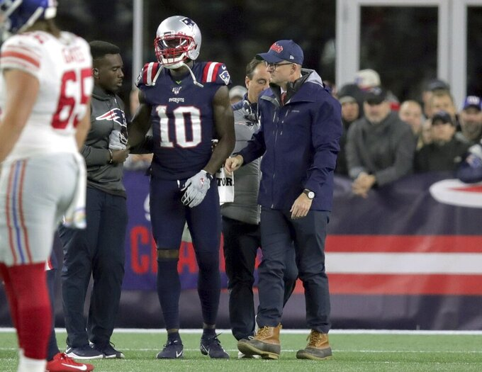 England Patriots wide receiver Josh Gordon is assisted from the field after an injury in the first half of an NFL football game against the New York Giants, Thursday, Oct. 10, 2019, in Foxborough, Mass. (AP Photo/Charles Krupa)