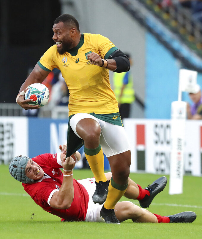 FILE - In this Sept. 29, 2019 file photo, Australia's Samu Kerevi is tackled by Wales' Jonathan Davies during the Rugby World Cup Pool D game at Tokyo Stadium between Australia and Wales in Tokyo, Japan. Kerevi has been named in the Australian 7's squad for the Tokyo Olympics. (AP Photo/Eugene Hoshiko,File)