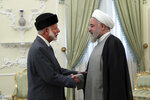 In this photo released by the official website of the office of the Iranian Presidency, Iranian President Hassan Rouhani, right, welcomes Omani Minister of State for Foreign Affairs Yusuf bin Alawi for their meeting in Tehran, Iran, Sunday, July 28, 2019. (Iranian Presidency Office via AP)