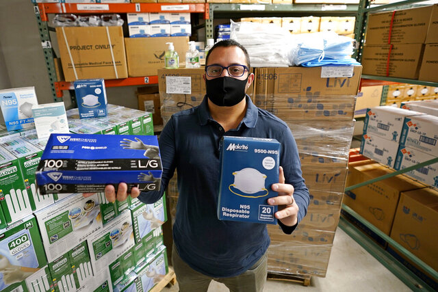 Ray Bellia holds up personal protective masks and gloves, used by medical and law enforcement professionals, in the warehouse of his Body Armor Outlet store, Wednesday, Dec. 9, 2020, in Salem, N.H. Bellia's store rapidly evolved into one of the nation's 20 largest suppliers of personal protective equipment to states this past spring, according to a nationwide analysis of state purchasing data by The Associated Press. (AP Photo/Charles Krupa)