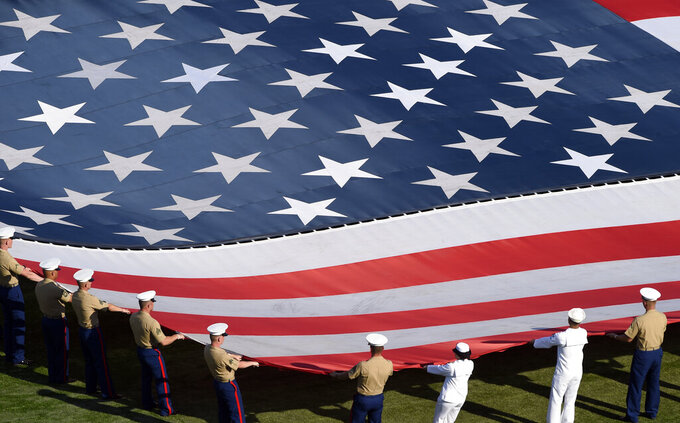 Active service members hold a large United States flag during pre-race activities before a NASCAR Cup Series auto race at Charlotte Motor Speedway in Concord, N.C., Sunday, May 26, 2019. (AP Photo/Mike McCarn)