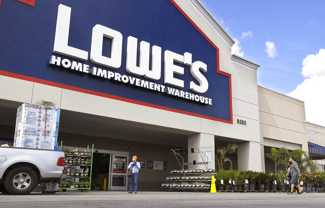 FILE-  In this March 22, 2020 file photo customers wearing masks walk into a Lowe's home improvement store in the Canoga Park section of Los Angeles. A massive surge in online sales and increased business at its U.S. stores helped push Lowe's second-quarter performance above analysts' estimates. Similar to rival Home Depot, Lowe's Cos. has experienced stronger interest in its products as people continue to stay home amid the virus outbreak.  (AP Photo/Mark J. Terrill, File)