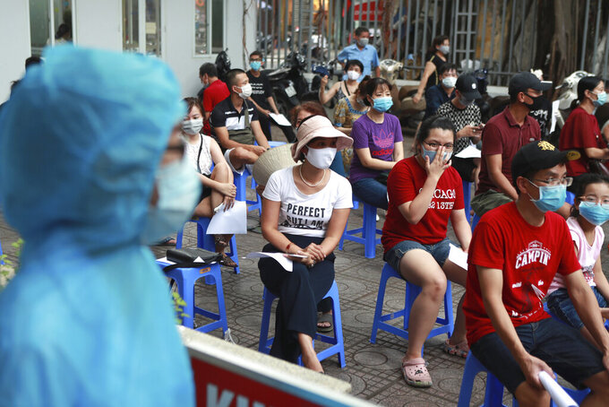 People wait in line for COVID-19 test in Hanoi, Vietnam, Friday, July 31, 2020. Vietnam reported on Friday the country's first ever death of a person with the coronavirus as it struggles with a renewed outbreak after 99 days without any cases. (AP Photo/Hau Dinh)
