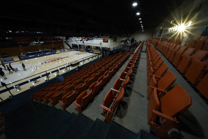 The sun shines through a window over empty seat as Gonzaga basketball players warm up before an NCAA college basketball game against Pepperdine on Saturday, Jan. 30, 2021, in Malibu, Calif. (AP Photo/Ashley Landis)