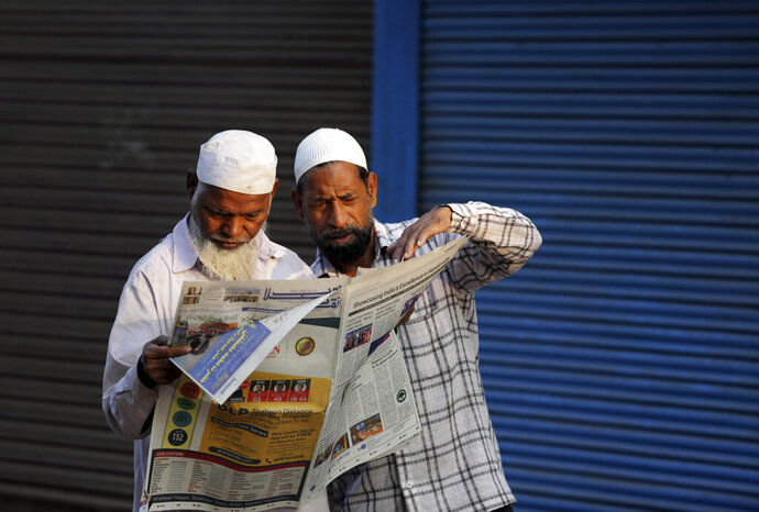 FILE - In this Sunday, Nov. 10, 2019, file photo, Muslims read about the verdict in a decades-old land title dispute between Muslims and Hindus in a newspaper in Ayodhya, India. India's largest Muslim political groups are divided over how to respond to a recent Supreme Court ruling that favors Hindus' right to a disputed site 27 years after Hindu nationalist mobs tore down a 16th-century mosque there, unleashing torrents of religious-motivated violence. (AP Photo/Rajesh Kumar Singh, File)
