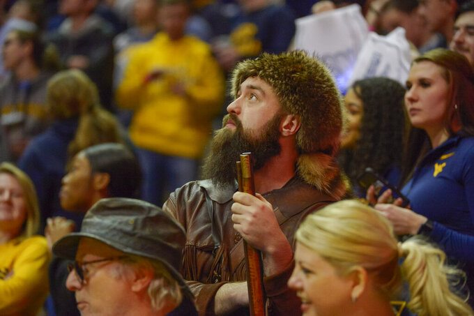 Mountaineer Mascot Trevor Kiess peers up at the scoreboard during the second half of an NCAA college basketball game against the University of Texas Longhorns in Morgantown, W.Va. on Saturday Feb. 9, 2019. (AP Photo/Craig Hudson)