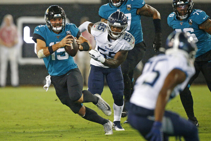 FILE - In this Sept. 19, 2019, file photo, Jacksonville Jaguars quarterback Gardner Minshew, left, scrambles away from Tennessee Titans inside linebacker Jayon Brown (55) during the first half of an NFL football game, in Jacksonville, Fla. Surviving in the NFL as a young quarterback means being able to move. That doesn't mean running as well as Lamar Jackson. Gardner Minshew, Kyle Allen and even Daniel Jones are showing that being able to elude pressure is a must to keep throwing the ball. (AP Photo/Stephen B. Morton, File)