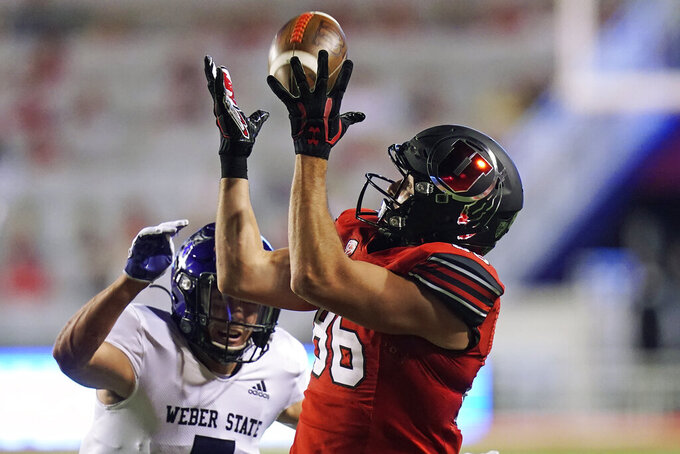 Utah tight end Dalton Kincaid (86) catches a pass as Weber State safety Preston Smith defends during the second half of an NCAA college football game Thursday, Sept. 2, 2021, in Salt Lake City. (AP Photo/Rick Bowmer)