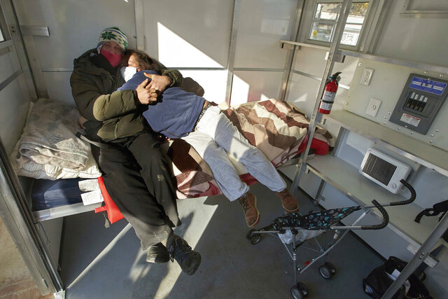Chris Foss, left, and Tiecha Vannoy embrace after moving into a new pod setup by the city in the Old Town district in Portland, Ore., Tuesday, Dec. 8, 2020. The pandemic has caught homeless service providers in a crosscurrent: demand is high, but their ability to provide services are constricted. Shelter operators who already cut capacity by half to meet social distance requirements face new stresses with winter looming. Coming in from the cold can now mean a night in a warehouse, an old Greyhound bus station, schools or an old jail. (AP Photo/Craig Mitchelldyer)