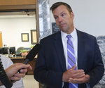 Kansas Secretary of Kris Kobach talks to reporters while a state board considers a challenge to independent gubernatorial candidate Greg Orman's spot on the ballot, Thursday, Aug. 23, 2018, in Topeka, Kan. Kobach is the Republican nominee for governor and his top deputy served as the elections board's chairman. (AP Photo/John Hanna)