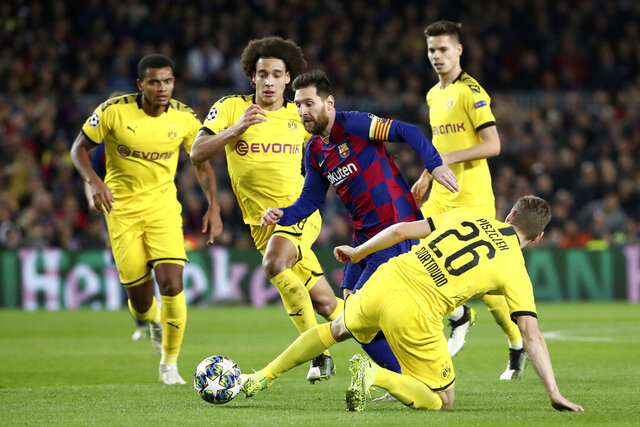 Barcelona's Lionel Messi drives the ball past Dortmund's Lukasz Piszczek, right, during a Champions League group F soccer match between Barcelona and Dortmund at the Camp Nou stadium in Barcelona, Spain, Wednesday, Nov. 27, 2019. (AP Photo/Emilio Morenatti)
