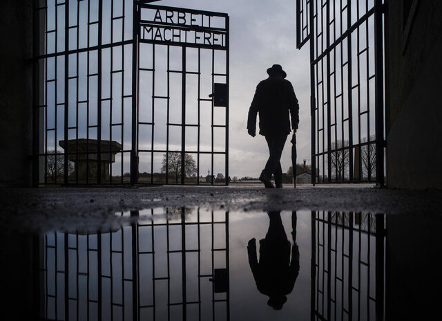 FILE - In this Jan. 27, 2019 file photo, a man walks through the gate of the Sachsenhausen Nazi death camp with the phrase