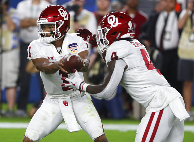 Oklahoma quarterback Kyler Murray (1) hands the ball to Oklahoma running back Trey Sermon (4), during the first half of the Orange Bowl NCAA college football game against Alabama, Saturday, Dec. 29, 2018, in Miami Gardens, Fla. (AP Photo/Wilfredo Lee)