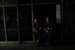 People wearing El Universal newspaper uniforms sit inside a darkened office building during a power outage in Caracas, Venezuela, Monday, March 25, 2019. The subway suspended service because of the power cuts Monday, as local media reported outages in at least six states. (AP Photo/Natacha Pisarenko)