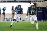 Michigan State's Jayden Reed, left, returns a punt for a touchdown as teammate Ben VanSumeren (13) blocks against Western Kentucky during the first quarter of an NCAA college football game, Saturday, Oct. 2, 2021, in East Lansing, Mich. (AP Photo/Al Goldis)