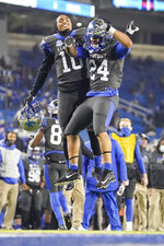 Kentucky running backs Asim Rose Jr. (10) and Chris Rodriguez Jr. (24) celebrate after Rodriguez scored a touchdown during the first half of the team's NCAA college football game against South Carolina, Saturday, Dec. 5, 2020, in Lexington, Ky. (AP Photo/Bryan Woolston)
