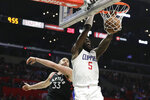 Los Angeles Clippers forward Montrezl Harrell, right, dunks past Toronto Raptors center Marc Gasol during the second half of an NBA basketball game in Los Angeles, Monday, Nov. 11, 2019. (AP Photo/Chris Carlson)