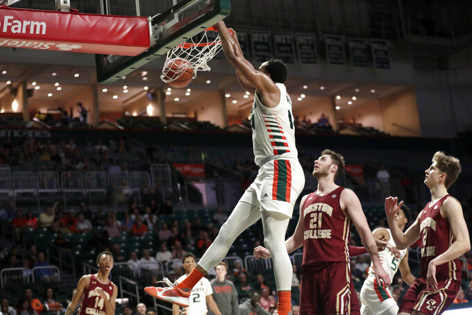Miami center Rodney Miller Jr., left dunks over Boston College forward Nik Popovic (21) and guard Julian Rishwain (2) during the second half of an NCAA college basketball game, Wednesday, Feb. 12, 2020, in Coral Gables, Fla. Miami won 85-58. (AP Photo/Lynne Sladky)