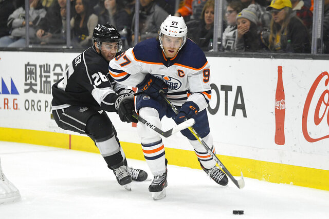 Edmonton Oilers center Connor McDavid, right, moves the puck while under pressure from Los Angeles Kings defenseman Sean Walker during the third period of an NHL hockey game Sunday, Feb. 23, 2020, in Los Angeles. The Oilers won 4-2. (AP Photo/Mark J. Terrill)