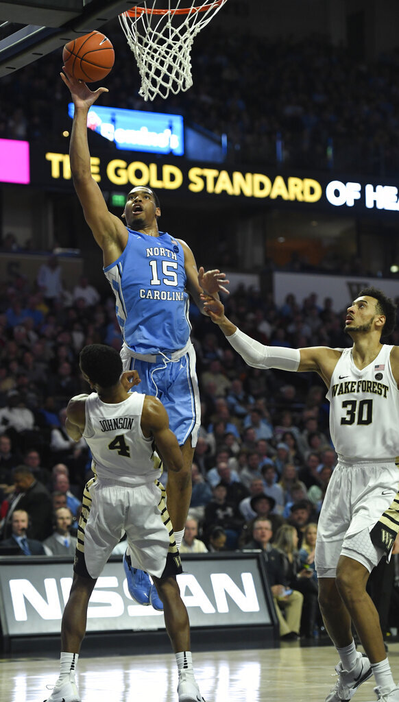 North Carolina's Garrison Brooks (15) commits a charge against Wake Forest's Torry Johnson (4) during the second half of an NCAA college basketball game in Winston-Salem, N.C.,  Saturday, Feb 16, 2019. (AP Photo/Woody Marshall)